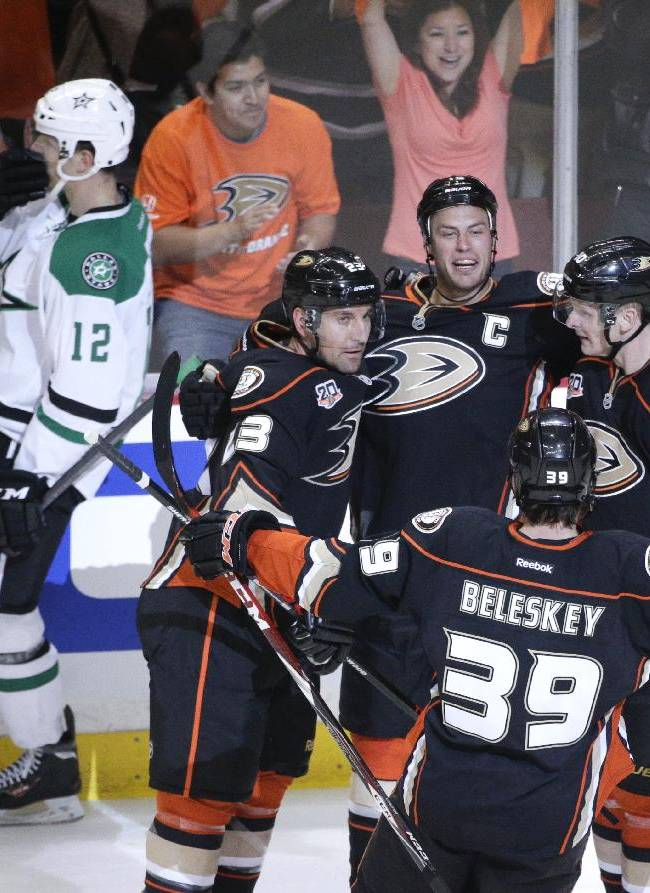 Anaheim Ducks' Ryan Getzlaf (15) celebrates his goal with Francois Beauchemin (23), Matt Beleskey (39) and Corey Perry (10) as Dallas Stars' Alex Chiasson (12) skates past them during the first period in Game 1 of the first-round NHL hockey Stanley Cup playoff series on Wednesday, April 16, 2014, in Anaheim, Calif