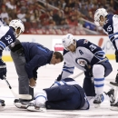 As a Winnipeg Jets training staff member checks on injured Evander Kane, teammates Dustin Byfuglien (33), Blake Wheeler (26) and Mark Scheifele (55) look on during the first period of an NHL hockey game against the Arizona Coyotes Thursday, Oct. 9, 2014,