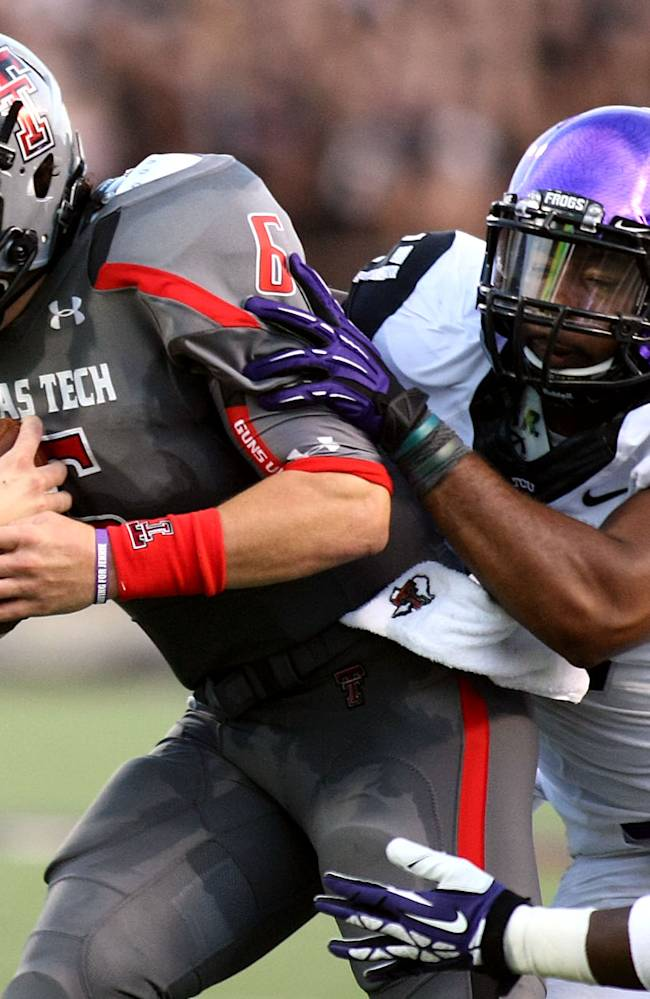 Texas Tech's Baker Mayfield, left, is tackled by TCU's Sam Carter, center, and Derrick Kindred during their NCAA college football game in Lubbock, Texas, Thursday, Sept. 12, 2013