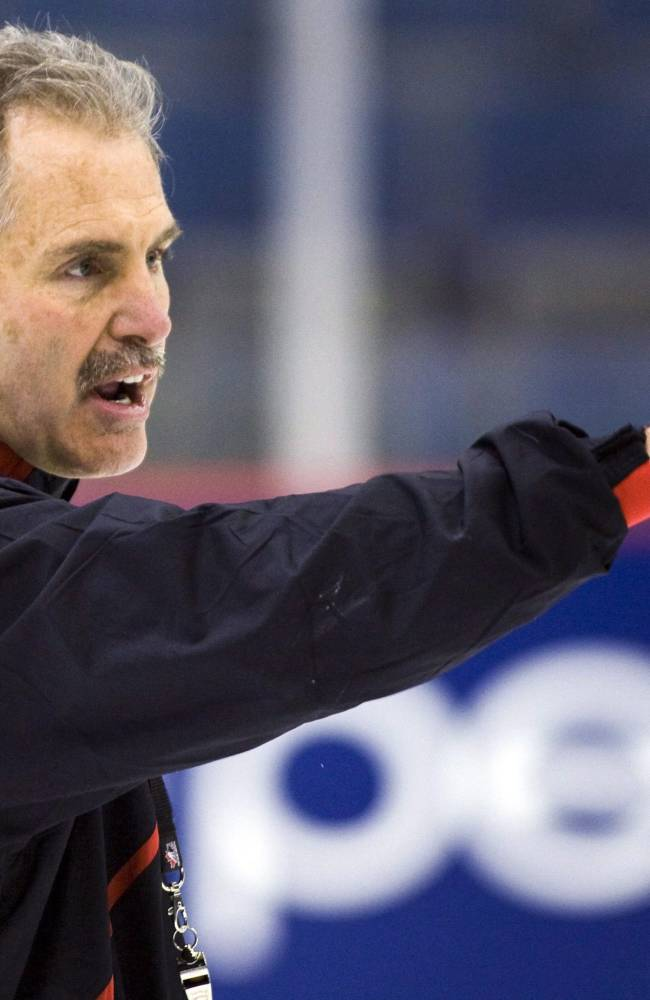 In this Dec. 14, 2009, photo, Canadian national junior team coach Willie Desjardins gives instructions during practice in Regina, Saskatchewan. The Vancouver Canucks hired Desjardins as coach on Monday, June 23, 2014