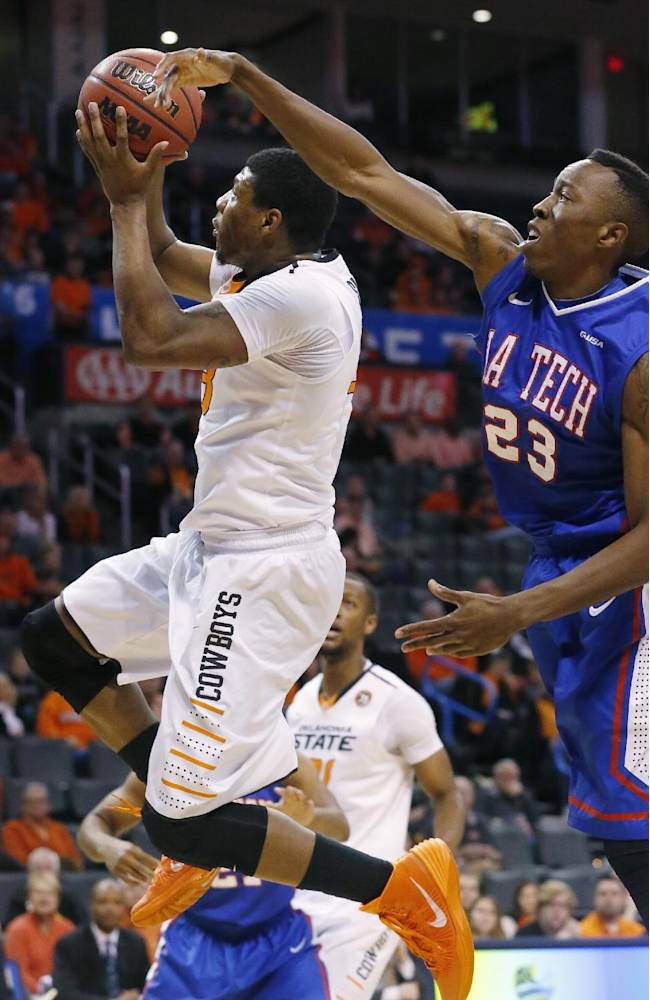 Oklahoma State guard Marcus Smart (33) shoots in front of Louisiana Tech guard Jaron Johnson (23) in the first half of an NCAA college basketball game in the All College Classic in Oklahoma City, Saturday, Dec. 14, 2013. Oklahoma won 70-55