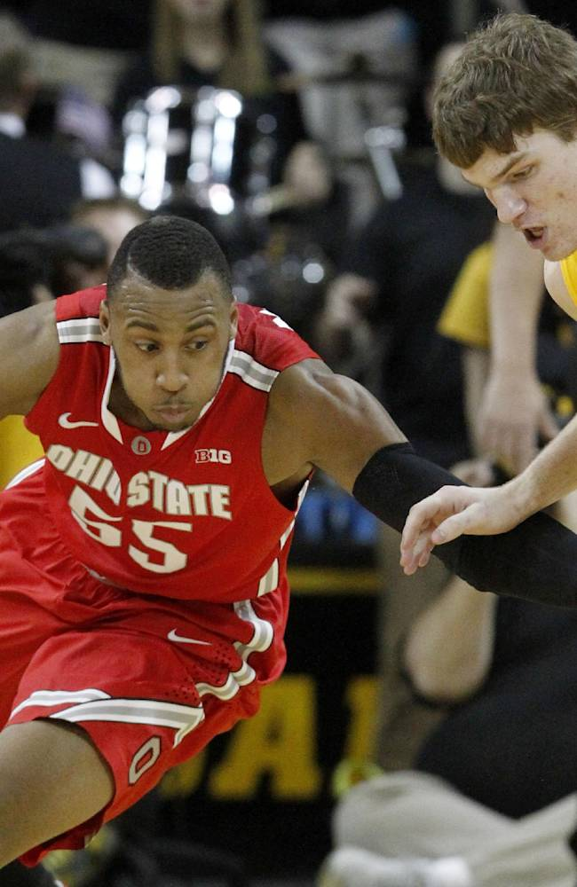 Ohio State center Trey McDonald (55) swats the ball away from Iowa center Adam Woodbury (34) during the first half of an NCAA college basketball game Tuesday, Feb. 4, 2014, in Iowa City, Iowa