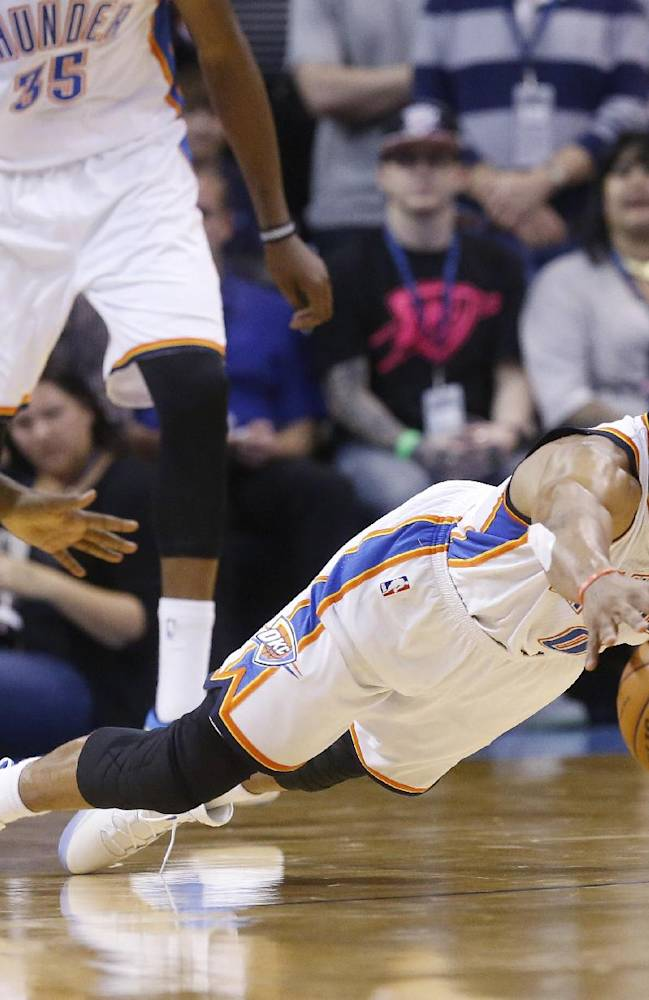 Oklahoma City Thunder guard Russell Westbrook (0) dives for a loose ball in front of Denver Nuggets guard Ty Lawson (3) in the fourth quarter of an NBA basketball game in Oklahoma City, Monday, Nov. 18, 2013. Oklahoma City won 115-113
