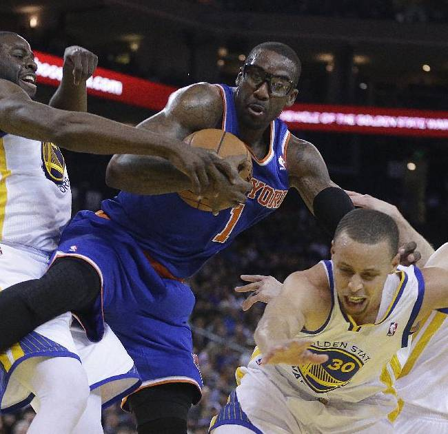 New York Knicks' Amar'e Stoudemire, center, drives the ball against Golden State Warriors' Draymond Green, left, Stephen Curry (30) and Steve Blake, right, during the second half of an NBA basketball game Sunday, March 30, 2014, in Oakland, Calif