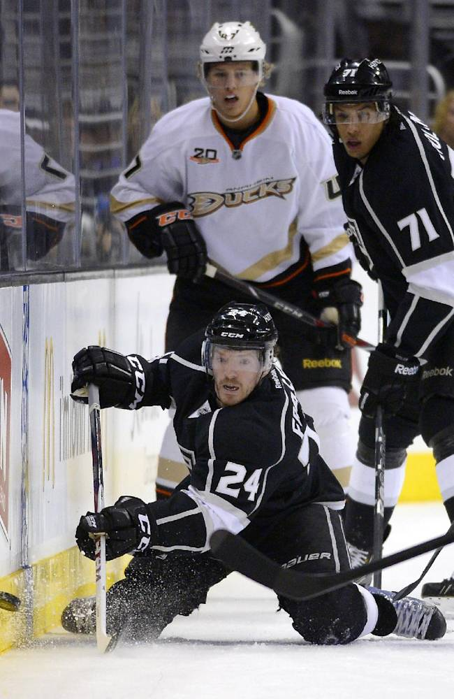 Los Angeles Kings center Colin Fraser, below, passes the puck from his knees as Anaheim Ducks defenseman Hampus Lindholm, upper left, and center Jordan Nolan watch during the first period of an NHL preseason hockey game, Tuesday, Sept. 24, 2013, in Los Angeles