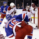 New York Rangers' Derick Brassard (16), front, scores on Phoenix Coyotes goalie Mike Smith, right, during the second period of the NHL hockey game, Monday, March 24, 2014, in New York The Associated Press