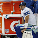 Dallas Cowboys quarterback Tony Romo seats on the beach as watches the action on the big screen television during the second half of an NFL football game against the Washington Redskins in Landover, Md., Sunday, Dec. 22, 2013 The Associated Press
