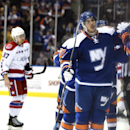 New York Islanders defenseman Travis Hamonic (3) celebrates his goal with teammates as Washington Capitals left wing Liam O'Brien (87) skates to his bench in the first period of an NHL hockey game at Nassau Coliseum on Wednesday, Nov. 26, 2014, in Unionda