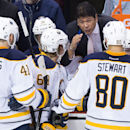 Buffalo Sabres coach Ted Nolane peaks to players including Andrej Meszaros (41), of Slovakia; Tyler Ennis (63) and Chris Stewart (80), during the third period of an NHL hockey game against the Vancouver Canucks on Friday, Jan. 30, 2015, in Vancouver, Brit
