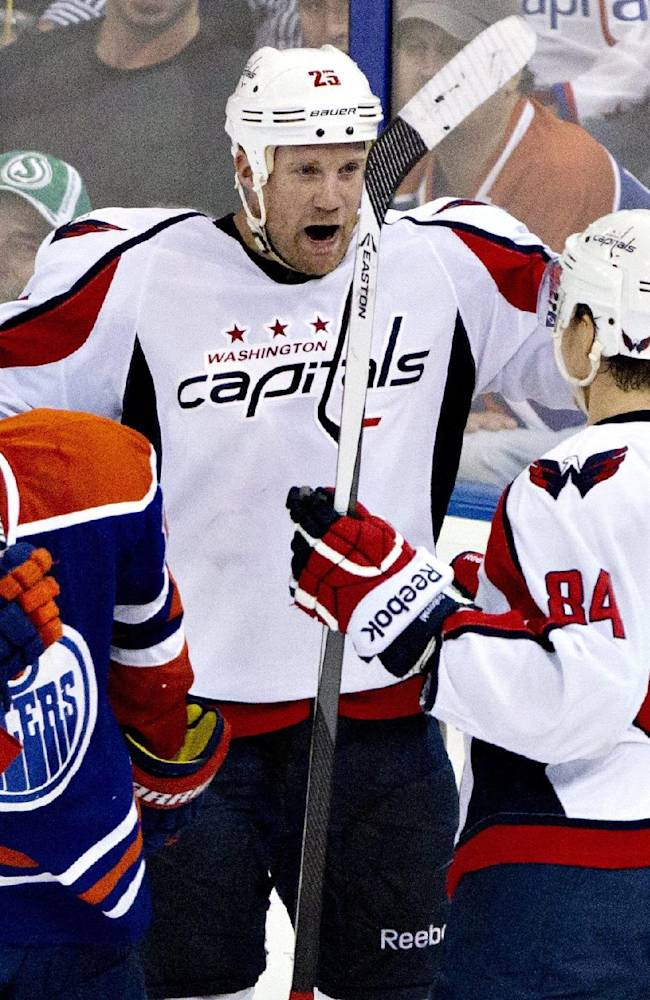 Washington Capitals' Jason Chimera (25) and Mikhail Grabovski (84) celebrate a goal as Edmonton Oilers' Nick Schultz (15) skates past during third period NHL hockey action in Edmonton, Alberta, on Thursday Oct. 24, 2013