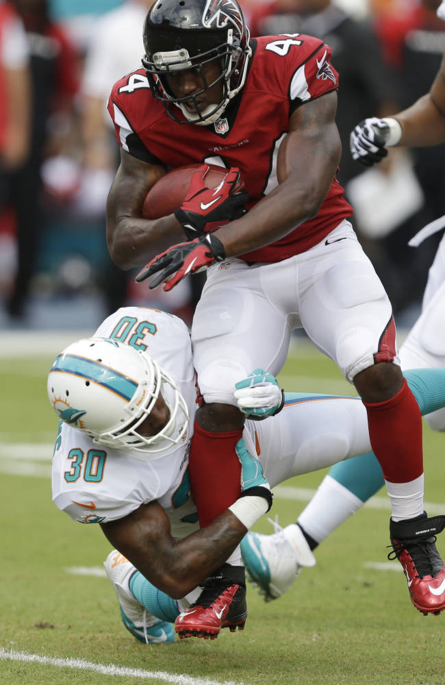 In this Sept. 22, 2013, file photo, Atlanta Falcons fullback Jason Snelling (44) is tackled by Miami Dolphins strong safety Chris Clemons (30) during the first half of an NFL football game in Miami Gardens, Fla. Snelling has been arrested on misdemeanor charges of marijuana possession and possession of drug paraphernalia. Winder, Ga., Police Officer Chris Cooper says Snelling was arrested early Friday morning, Nov. 15, 2013, following a traffic stop