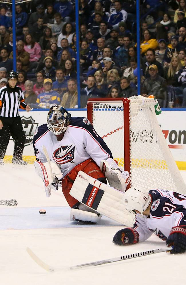 St. Louis Blues center David Backes (right) hops over Columbus Blue Jackets defenseman James Wisniewski (21) after taking a shot at Columbus Blue Jackets goaltender Curtis McElhinney in third period action of an NHL hockey game Saturday, Jan. 4, 2014, in St. Louis