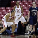 Maryland's Malina Howard, left, and Alicia DeVaughn, center, celebratea alongside Quinnipiac forward Camryn Warner after DeVaughn was fouled as she scored a basket during the first half of a first-round game in the women's NCAA college basketball tournament in College Park, Md., Saturday, March 23, 2013. (AP Photo/Patrick Semansky)