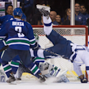 Tampa Bay Lightning's Steven Stamkos, right, is tripped up as Vancouver Canucks' goalie Eddie Lack, of Sweden, makes the save while Kevin Bieksa (3) watches during the first period of an NHL hockey game Saturday, Oct. 18, 2014, in Vancouver, British Colum