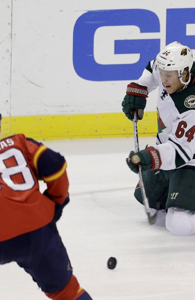Minnesota Wild's Mikael Granlund (64) goes down as he drives against Florida Panthers' Shawn Matthias (18) in the first period of an NHL hockey game on Saturday, Oct. 19, 2013, in Sunrise, Fla