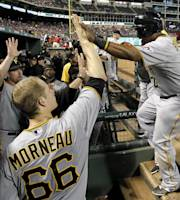 Pittsburgh Pirates' Marlon Byrd, right, is congratulated in the dugout by Justin Morneau (66) and others after scoring on a double by Pedro Alvarez in the seventh  inning of a baseball game against the Texas Rangers, Monday, Sept. 9, 2013, in Arlington, Texas. (AP Photo/Tony Gutierrez)