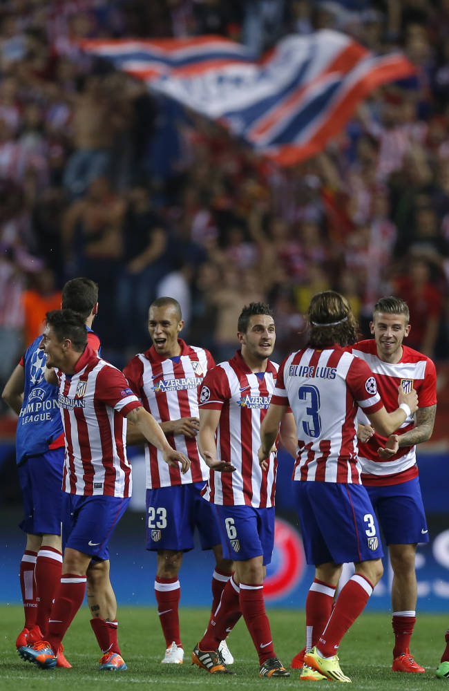Atletico's players celebrate at the end of the Champions League quarterfinal second leg soccer match between Atletico Madrid and FC Barcelona at the Vicente Calderon stadium in Madrid, Spain, Wednesday, April 9, 2014. (AP Photo/Andres Kudacki)