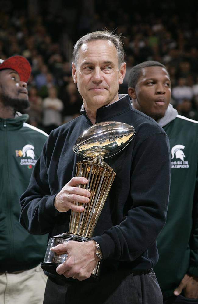 Michigan State football coach Mark Dantonio holds the 100th Rose Bowl championship trophy at an NCAA college basketball game between Michigan State and Ohio State, Tuesday, Jan. 7, 2014, in East Lansing, Mich