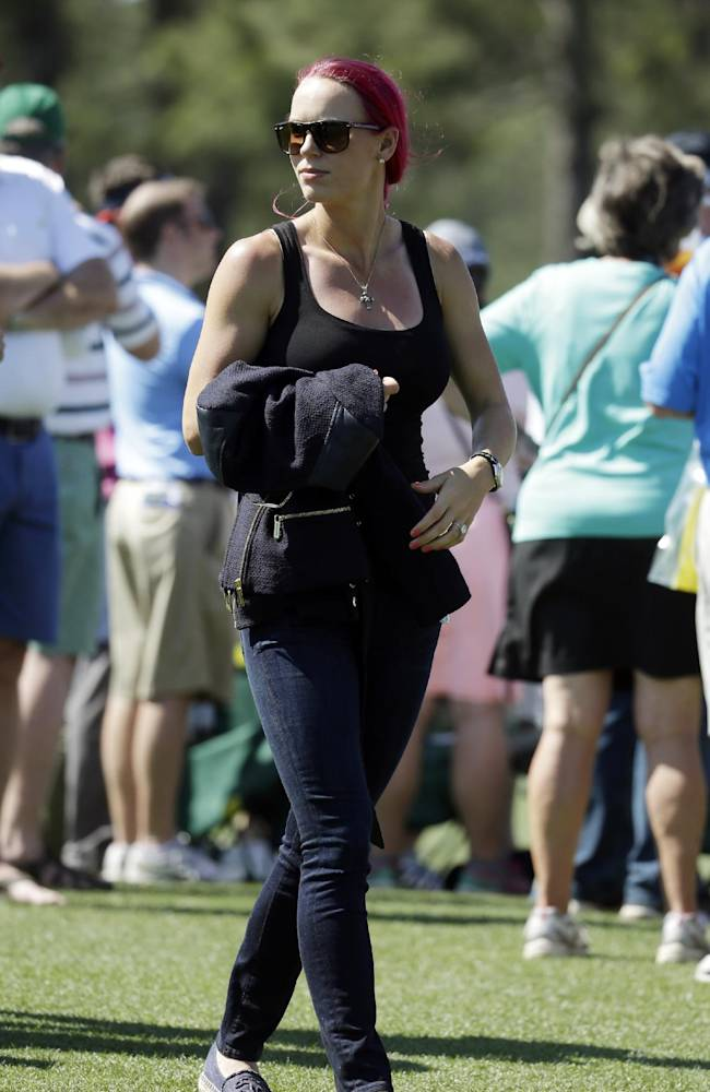 Tennis player Caroline Wozniacki watches her fiancee Rory McIlroy, of Northern Ireland, during the first round of the Masters golf tournament Thursday, April 10, 2014, in Augusta, Ga