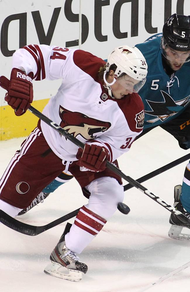 Phoenix Coyotes' Tim Kennedy (34) and San Jose Sharks' Jason Demers vie for the puck during the first period of an NHL preseason hockey game in San Jose, Calif., Saturday, Sept. 21, 2013