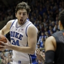 Duke's Ryan Kelly (34) drives to the basket as Miami's Shane Larkin (0) defends during the first half of an NCAA college basketball game in Durham, N.C., Saturday, March 2, 2013. Duke won 79-76. (AP Photo/Gerry Broome)