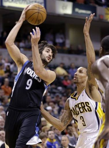 Minnesota Timberwolves guard Ricky Rubio, left, passes over Indiana Pacers guard George Hill in the first half of an NBA basketball game in Indianapolis, Wednesday, March 13, 2013