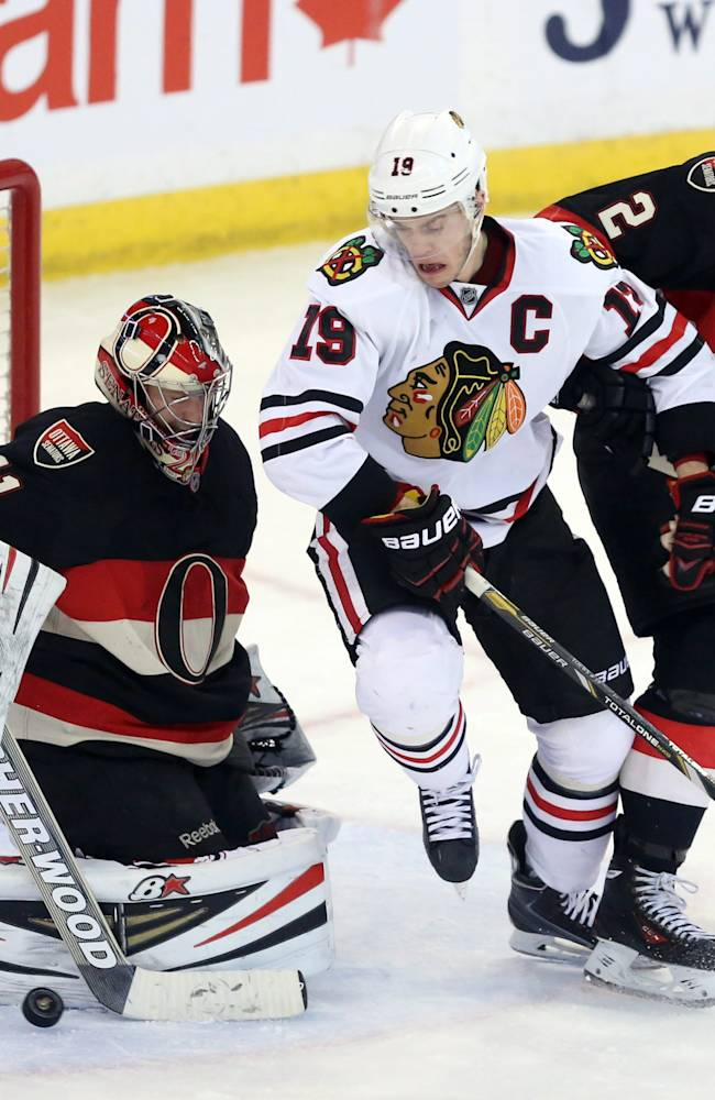 Ottawa Senators goaltender Craig Anderson (41) clears the puck as teammate Jared Cowen (2) and Chicago Blackhawks' Jonathan Toews (19) battle in front of the net during second-period NHL hockey game action in Ottawa, Ontario, Friday, March 28, 2014