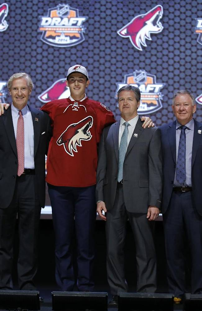 Brendan Perlini stands with Arizona Coyotes officials after being chosen 12th overall during the first round of the NHL hockey draft, Friday, June 27, 2014, in Philadelphia