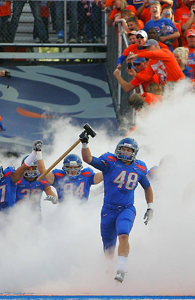 In this Oct. 9, 2010, file photo, Boise State's J.C. Percy leads his teammates onto the field for an NCAA college football game against Toledo in Boise, Idaho. Boise State president Bob Kustra argued in an op-ed sent to various media outlets last week that adding new benefits for athletes in the big conferences only serves to make them look more like professional leagues and will lead to larger and larger athletic budgets