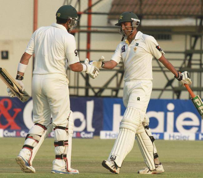 Pakistan batsman  Younis Khan, right, shakes hands with fellow batsman Misbal ul Haqu after scoring 50 runs on the  second day of the last  test match of the series  against Zimbabwe at Harare Sports Club  in Harare,Wednesday, Sept, 11, 2013