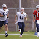 New England Patriots quarterback Tom Brady (12) runs with wide receiver Julian Edelman (11) and oftensive lineman Ryan Wendell (62) during a stretching session before practice begins at the NFL football team's facility Wednesday, Oct. 29, 2014 in Foxborou