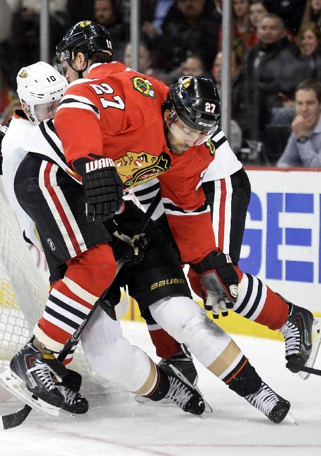 Chicago Blackhawks defenseman Johnny Oduya (27) and center Jonathan Toews, back, knock Anaheim Ducks right wing Corey Perry off the puck during the first period of an NHL hockey game Friday, Dec. 6, 2013 in Chicago