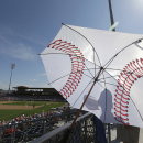 An usher is shielded from the sun by an umbrella during a spring training baseball exhibition game between the Philadelphia Phillies and New York Yankees, Tuesday, March 3, 2015, in Clearwater, Fla. (AP Photo/Lynne Sladky)