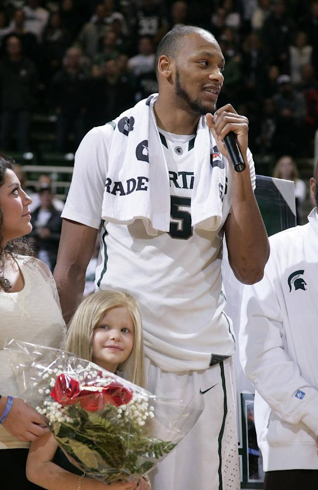 Michigan State senior Adreian Payne addresses the crowd during a senior day ceremony as he stands with his guest, Lacey Holsworth, an 8-year-old from St. Johns, Mich., who is battling cancer, following an NCAA college basketball game against Iowa, Thursday, March 6, 2014, in East Lansing, Mich. Michigan State won 86-76