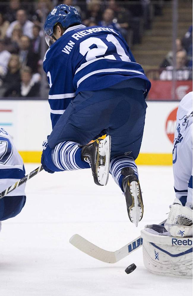 Tampa Bay Lightning goaltender Ben Bishop makes a save as he is screened by leaping Toronto Maple Leafs left winger James van Riemsdyk (21) and defenseman Radko Gudas (7) during second period NHL action in Toronto on Wednesday March 19, 2014