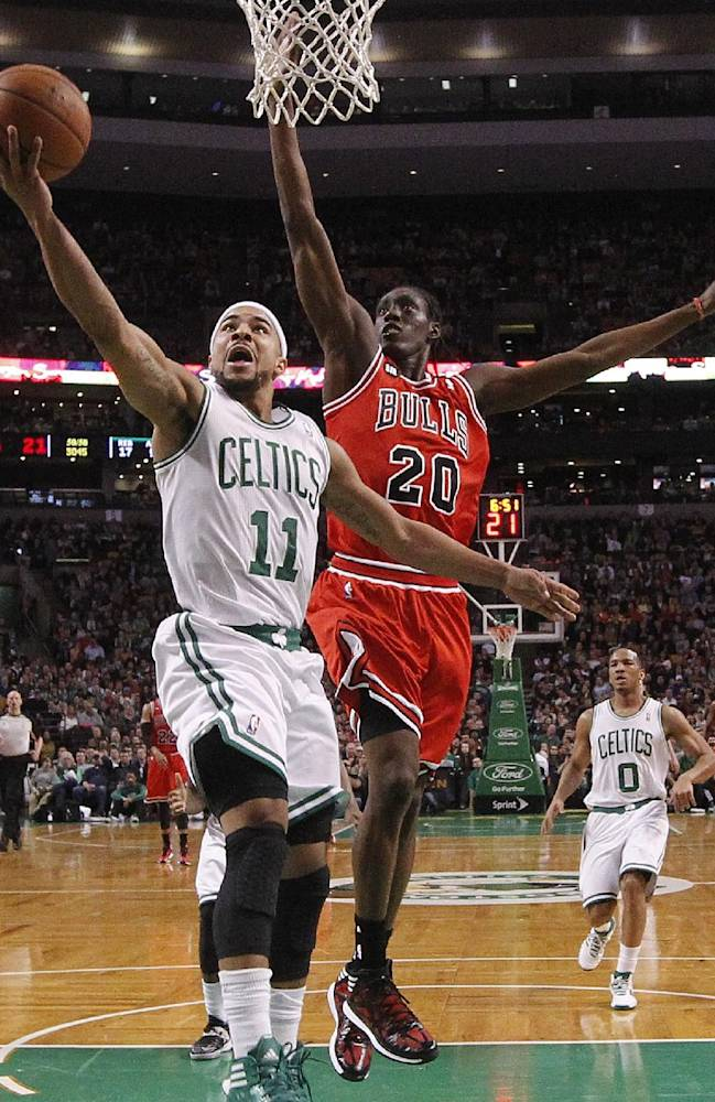 Boston Celtics' Jerryd Bayless (11) shoots in front of Chicago Bulls' Tony Snell (20) in the second quarter of an NBA basketball game in Boston, Sunday, March 30, 2014