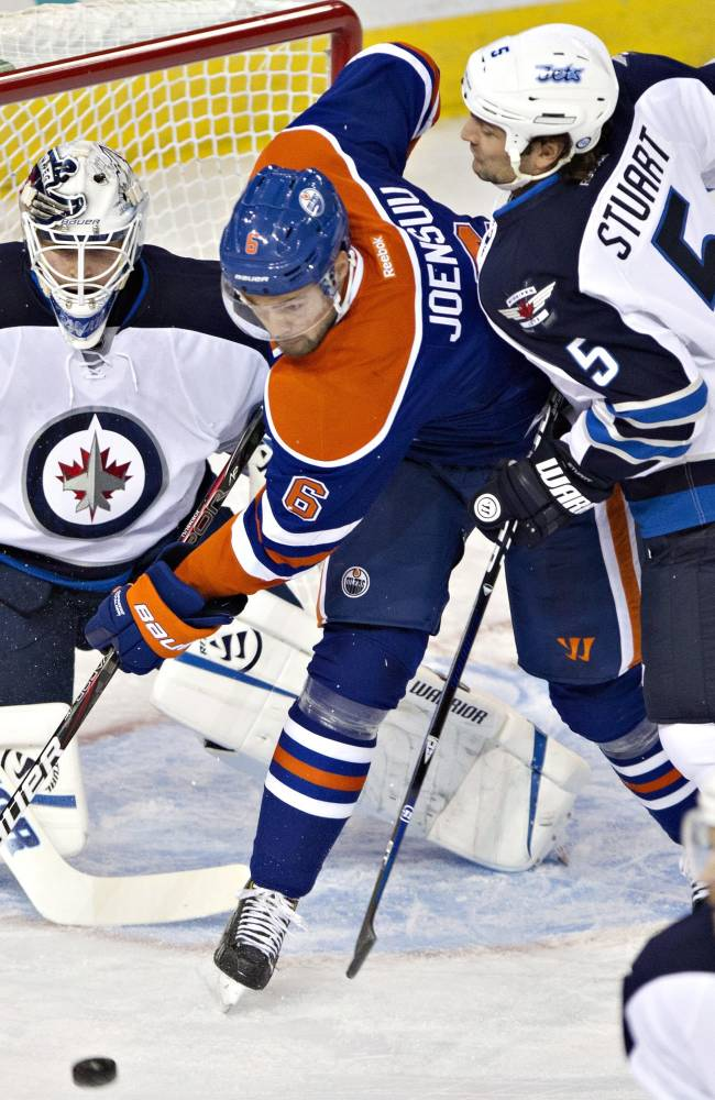 Winnipeg Jets goalie Edward Pasquale (32) watches as Mark Stuart (5) and Edmonton Oilers' Jesse Joensuu (6) look for a rebound during the first period of an NHL hockey preseason game Monday, Sept. 23, 2013, in Edmonton, Alberta