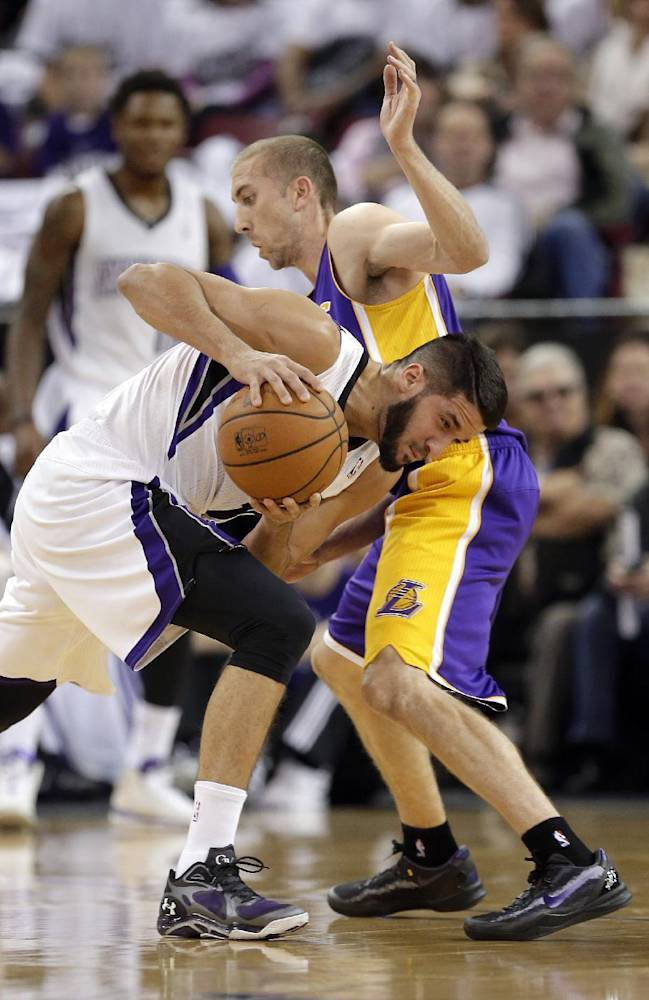 Sacramento Kings guard Greivis Vasquez, left, of Venezuela, ducks under the arm of Los Angeles Lakers guard Steve Blake as he drives during the first quarter of an NBA basketball game in Sacramento, Calif., Friday, Dec. 6, 2013