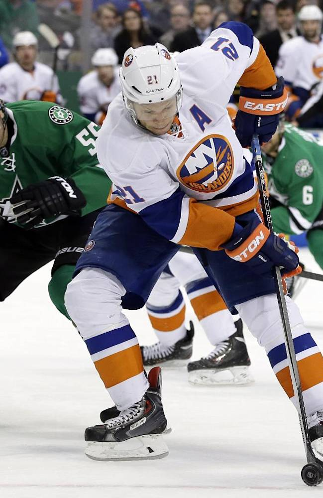 New York Islanders right wing Kyle Okposo (21) controls the puck on his way to the net for a shot attempt as Dallas Stars defenseman Sergei Gonchar (55), of Russia, defends in the second period of an NHL hockey game, Sunday, Jan. 12, 2014, in Dallas