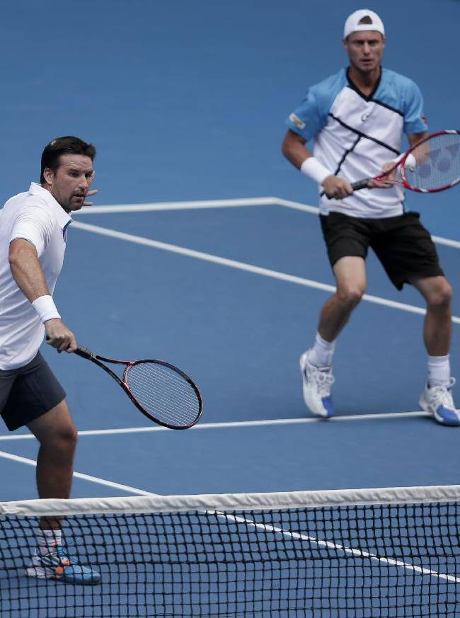 Australian players Pat Rafter, left, and Lleyton Hewitt play against Eric Butorac of the U.S and Klaasen Raven of South Africa in a first round doubles match at the Australian Open tennis championship in Melbourne, Australia, Wednesday, Jan. 15, 2014