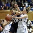 Monmouth's Chevannah Paalvast (10) wrestles a rebound away from Duke 's Haley Peters (33) during the first half of an NCAA women's college basketball game in Durham, N.C., Sunday, Dec. 30, 2012. Duke's Tricia Liston (32) watches the play. (AP Photo/Bob Leverone)