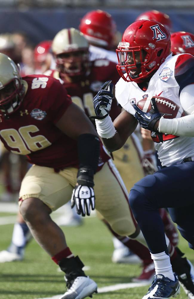 Arizona running back Ka'Deem Carey (25) rushes up field asile Boston College defensive lineman Kaleb Ramsey (96) pursues during the first half of the AdvoCare V100 Bowl NCAA college football game, Tuesday, Dec. 31, 2013, at Independence Stadium in Shreveport, La