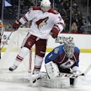 Phoenix Coyotes left wing Tim Kennedy (34) hops behind Colorado Avalanche goalie Semyon Varlamov, of Russia, (1) during the second period of an NHL hockey game in Denver on Tuesday, Dec. 10, 2013. (AP Photo/Joe Mahoney)