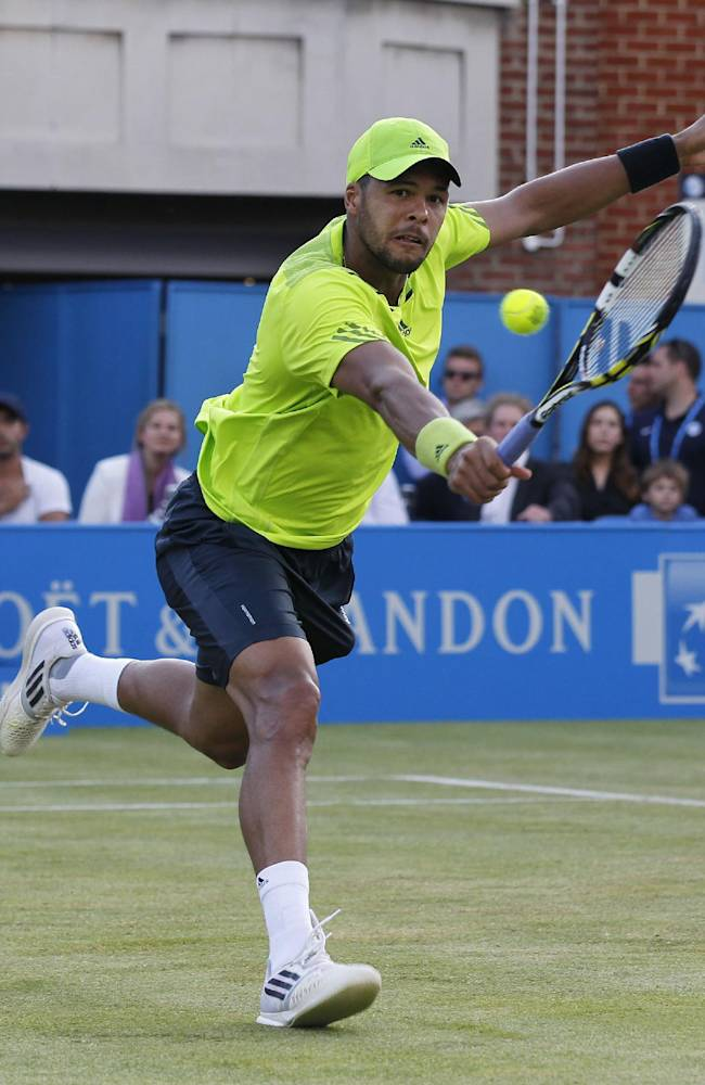 Jo-Wilfried Tsonga of France plays a return to Marinko Matosevic of Australia during their Queen's Club grass court championships 3rd round tennis match in London, Thursday, June 12, 2014