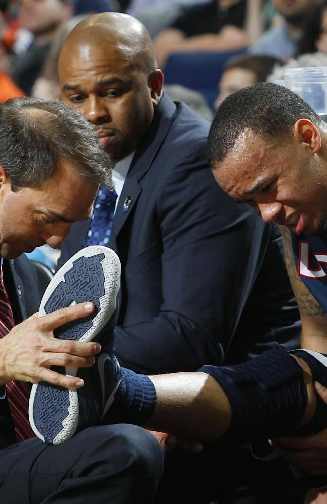 A trainer helps Connecticut's Shabazz Napier (13) after he was hurt on a play during the second half of a third-round game against Villanova in the NCAA men's college basketball tournament in Buffalo, N.Y., Saturday, March 22, 2014. Connecticut won the game 77-65