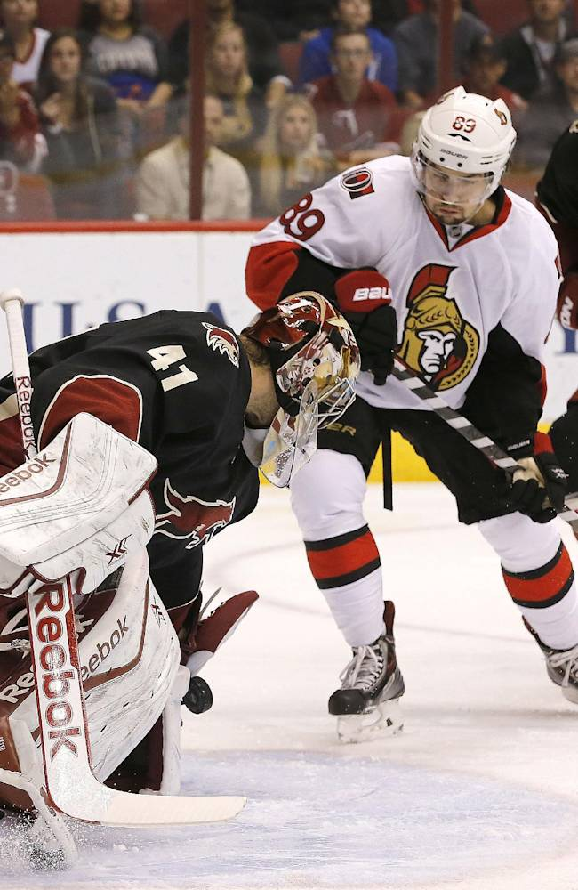 Phoenix Coyotes' Mike Smith (41) makes a save on a shot by by Ottawa Senators' Cory Conacher (89) during the first period in an NHL hockey game Tuesday, Oct. 15, 2013, in Glendale, Ariz