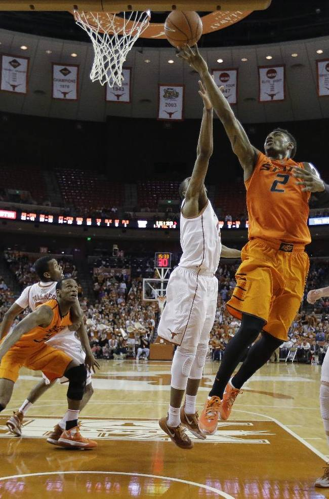 Oklahoma State's Le'Bryan Nash (2) drives between Texas' Prince Ibeh (44) and Connor Lammert (21) to score during the second half on an NCAA college basketball game, Tuesday,  Feb. 11, 2014, in Austin, Texas. Texas won 87-68