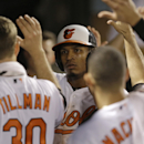 Baltimore Orioles' Jimmy Paredes, center, high-fives teammates in the dugout after scoring on a sacrifice fly ball by Chris Davis in the sixth inning of a baseball game against the Houston Astros, Tuesday, May 26, 2015, in Baltimore. (AP Photo/Patrick Semansky)