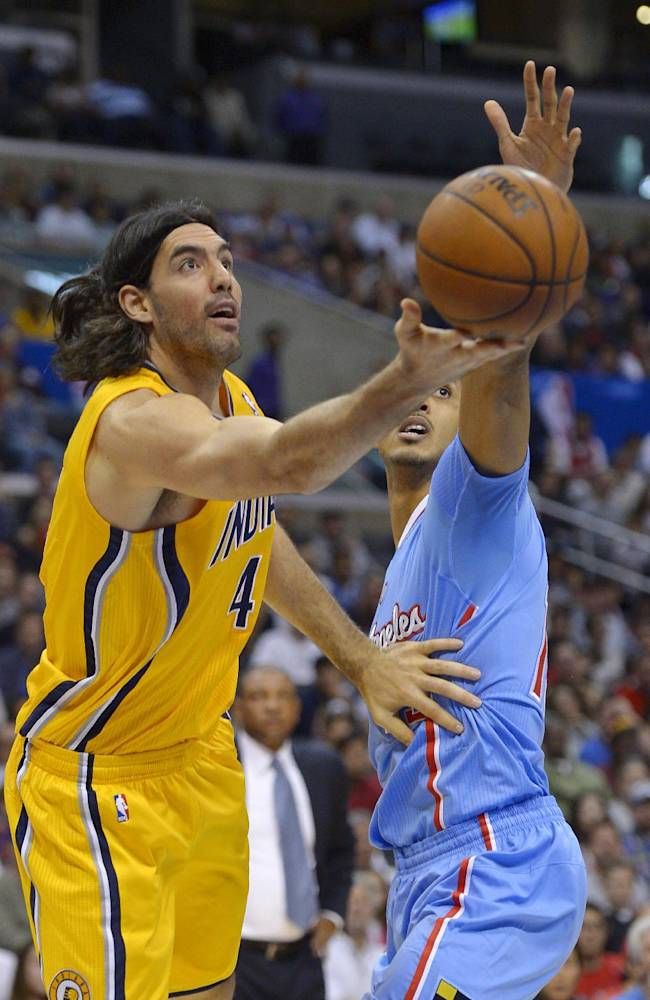 Indiana Pacers forward Luis Scola, left, of Argentina, puts up a shot as Los Angeles Clippers center Ryan Hollins defends during the first half of an NBA basketball game, Sunday, Dec. 1, 2013, in Los Angeles