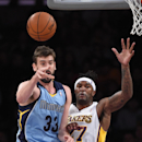Memphis Grizzlies center Marc Gasol, left, of Spain, passes the ball under pressure from Los Angeles Lakers forward Jordan Hill during the first half of an NBA basketball game, Sunday, April 13, 2014, in Los Angeles The Associated Press